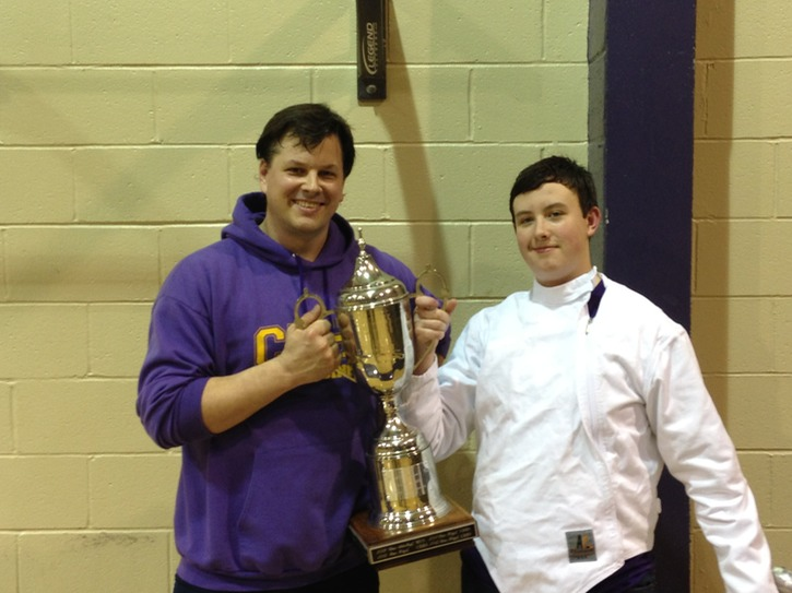 Coach Tom (L) and victorious Capt. Devin Geiger (R) hold the St. Michael's Cup after a close duel with MUS!